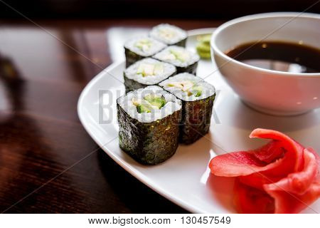 Rolls in nori seaweed with avocado pickled ginger and soy sauce. Asian cuisine traditional dish - sushi.