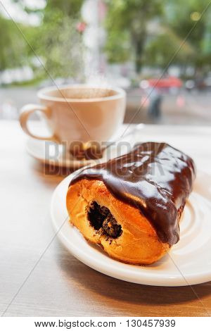 Tasty bun with chocolate icing and poppy filling. White mug with hot coffee on background.