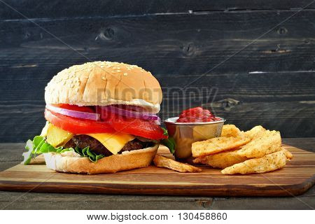Classic Hamburger With With Potato Wedges Over A Dark Wood Background