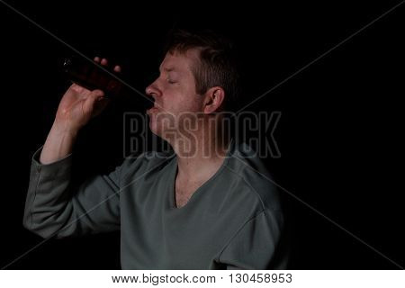 Depressed man drinking beer out of a bottle while sitting down with eyes close in a dark background.