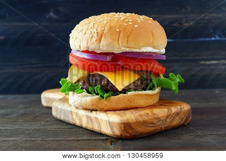 Classic Hamburger With Onions, Tomato, Cheese And Lettuce On A Paddle Board Over Dark Wood