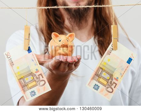 Savings concept. Young handsome long haired man holding piggybank moneybox around banknotes cash.