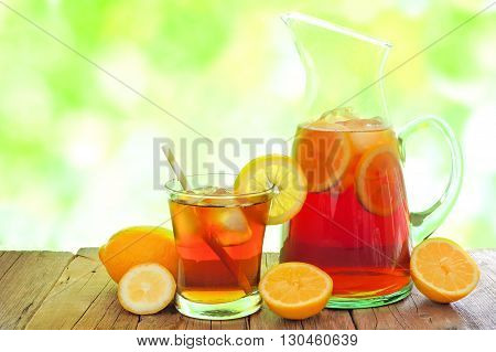 Pitcher Of Iced Tea With Glass And Lemon Slices Against A Defocused Outdoors Background