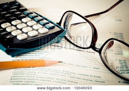 Eye Glasses On An Accounting Book With Pencil And Calculator