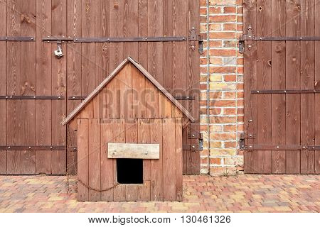 Wooden kennel in front of a barn with chain and dog inside.