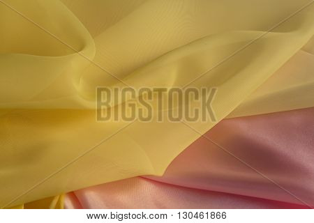thin yellow fabric on a pink silk background