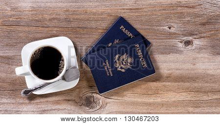 Dark coffee and passports for travel plans on rustic wood.