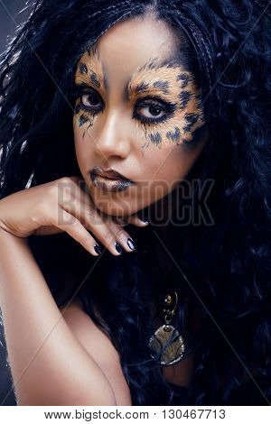 beauty afro girl with cat make up, creative leopard print on face closeup halloween woman