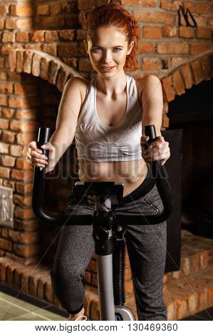 Active Young Woman Doing Exercise On Bicycle At Home.