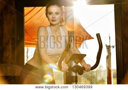 Active Young Woman Doing Exercise Bike At Home, In The Rays Of T