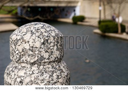 Close up of granite post with a bridge, park, and water in background