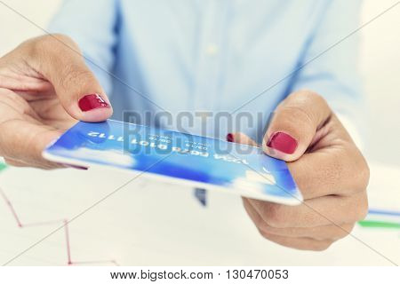 closeup of a young caucasian woman, wearing red polished fingernails, with a simulated credit card in her hands, sitting at an office desk