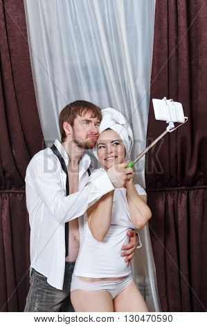 Husband and wife make fun selfie. Girl with a towel over his head. Marital time. After a night in a hotel. Selfie stick.