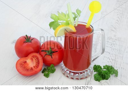 Tomato juice health drink with lemon, celery and parsley over distressed wood background. High in vitamins, anthocyanins and antioxidants.