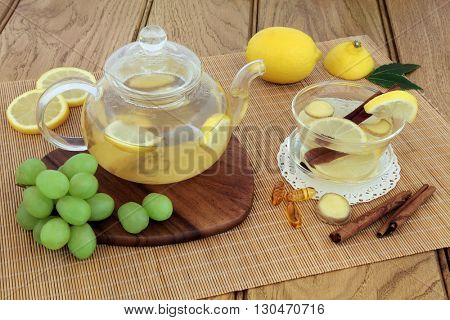 Cold and flu remedy with hot lemon, honey and ginger drink in glass tea cup and teapot, with grapes, spices and  multi vitamin tablets on maple board over bamboo and oak background.