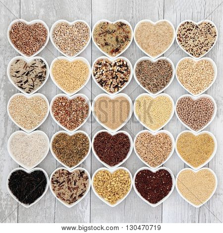 Healthy grain food selection in heart shaped porcelain bowls over distressed white wood background.