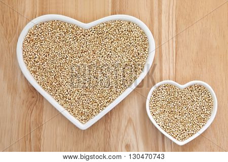 Quinoa grain super food in heart shaped porcelain dishes over beech wood background.