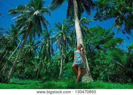 Attractive young woman outdoors with palm trees background