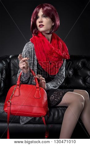 Woman modeling spring fashion and a red hand bag on a black leather couch