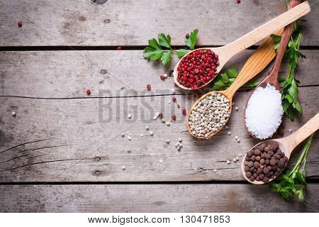 Seasoning for cooking. Red white and allspice pepper and sea salt in wooden spoon on aged wooden background. Food ingredient. Selective focus. Place for text. Flat lay. Top view.