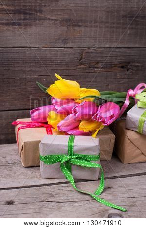 Bunch of yellow and pink spring tulips flowers and boxes with presents on vintage wooden background. Selective focus. Place for text.