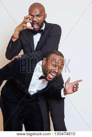 two afro-american businessmen in black suits emotional posing, gesturing, smiling. wearing bow-ties