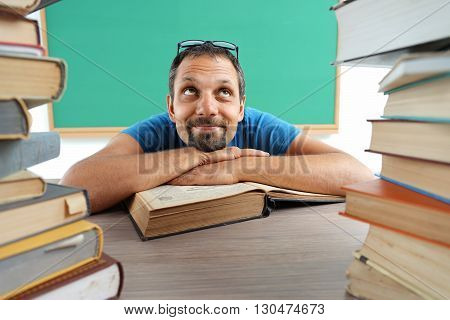 Fantasy pupil looking up as if daydreaming or thinking of something pleasant while sitting at the desk with open book. Photo of man creative concept with Back to school theme