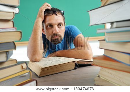 Adult teacher at a loss or thinking something. Photo adult man surrounded by books education concept