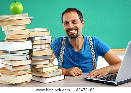 Happy smiling teacher at the classroom working with computer. Photo of smiling teacher creative concept with Back to school theme