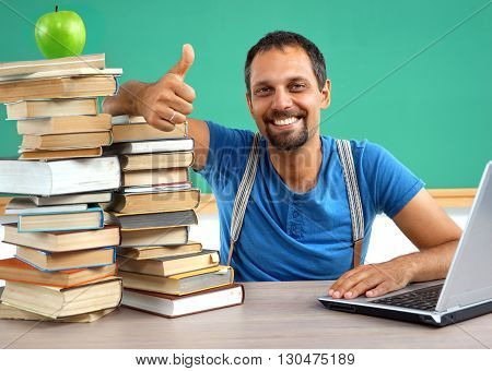Happy smiling man showing thumbs up gesture. Photo of smiling teacher creative concept with Back to school theme