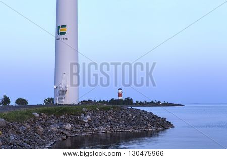 UMEA, SWEDEN ON JUNE 02. Closeup view on an Umea Energy wind power pylon and a lighthouse on June 02, 2013 in Holmsund, Sweden. Pier, gravel road and evening by the sea. Editorial use.