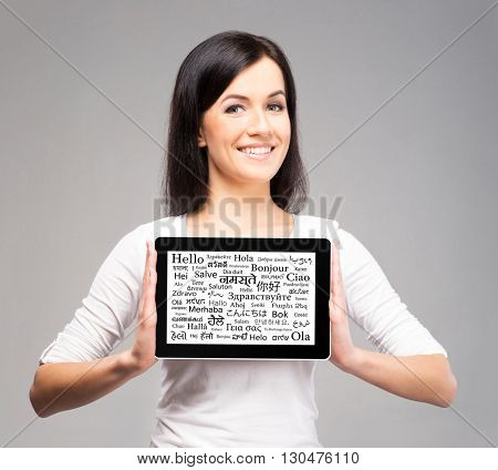 Beautiful female showing tablet on isolated background. Learning different languages concept.