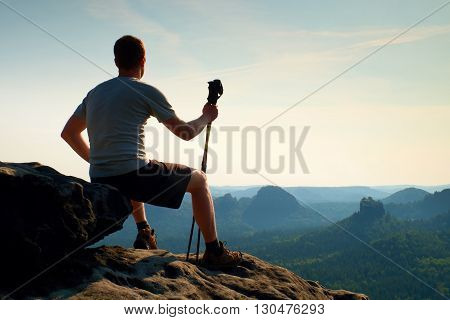Tired Sitting Tourist With Poles In Hand. Sunny Spring Daybreak In Rocky Mountains. Hiker With Track