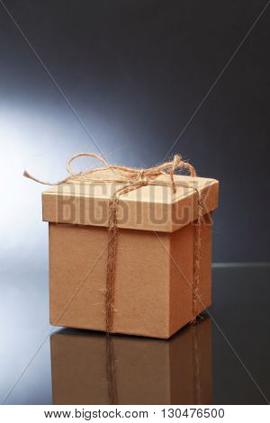 Cardboard box tied with twine on dark background