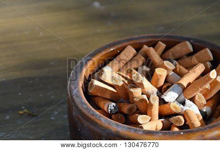 cigarette filter in ceramic ashtray on desk