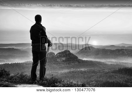 Silhouette Of Tourist Guide With Poles In Hand. Hiker With Sporty Sportswear Stand On Sharp View Poi
