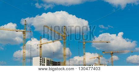 Construction cranes on a background of the summer sky with clouds