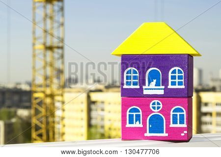 Wooden house on a background of construction