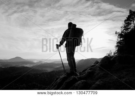 Tourist with heavy backpack and poles in hands stand on rocky view point and watching down to deep misty valley bellow. Sunny spring daybreak in rocky mountains.