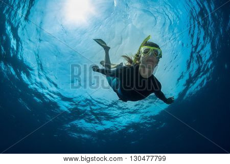 Close up underwater shot of the lady free-diver in yellow mask