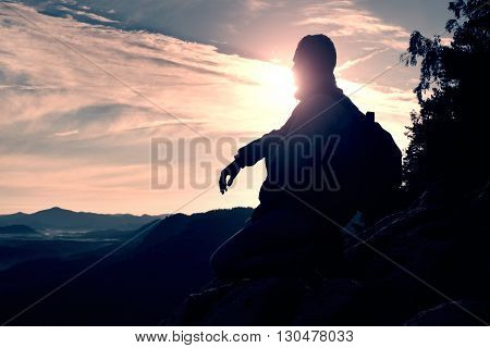 Tourist with sporty backpack sit on rocky peak and watching into deep misty valley bellow. Sunny spring daybreak in rocky mountains.