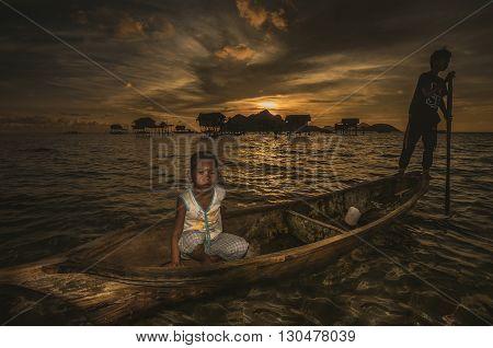 Maiga Island Sabah Malaysia - April 29 2016 : A shot of two children in a wooden boat taken at Maiga Island Sabah Malaysia during sunrise.