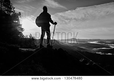 Tourist with backpack stand on rocky view point and watching into deep misty valley bellow.