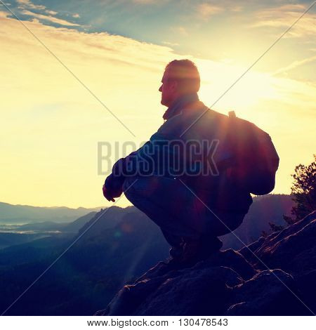 Hiker With Sporty Backpack Sit On Rocky Cliff Edge And Watching Into Misty Valley Bellow. Sunny Spri
