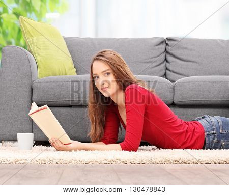 Young brunette woman laying on the floor and reading a book at home