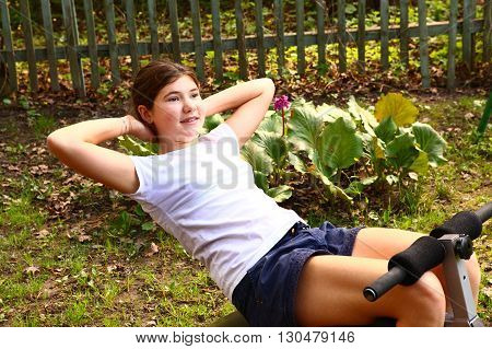 teen pretty girl work out stomach exercise on the outdoor summer garden background