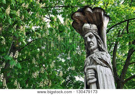 Old carved wooden sculpture Duke Vytautas against a background of flowering chestnut trees. Grodno Belarus.