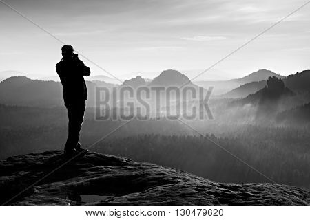 Professional Photographer Takes Photos With Big Camera On Rock. Dangerous Possition At End Of Cliff.