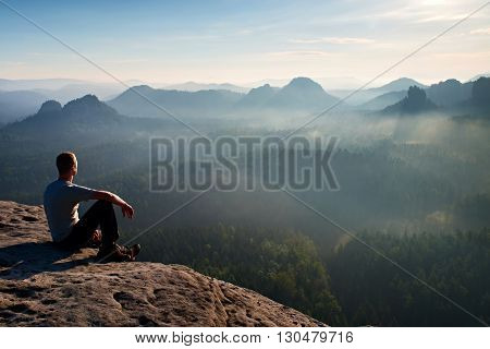 Tall Short Hair Hiker In Light Shirt Sit On A Rock And Enjoy Foggy  Mountain Scenery
