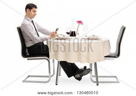 Sad man looking at his cell phone seated at a restaurant table isolated on white background